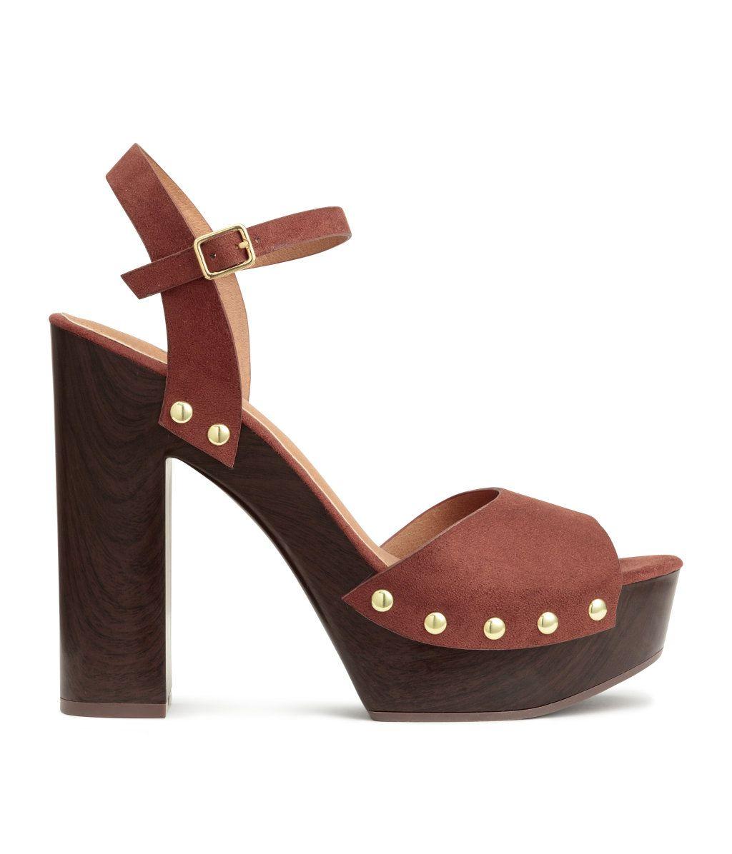 Rustbrun. Et par platåsandaletter i semsket skinnimitasjon med metallnagler. Sandalettene har regulerbar vristrem med elastikk og metallspenne. Fôr og
