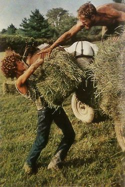 justenoughisplenty:  Bucking hay bales, a couple shares the work of a small diversified farm in Vermont, near New Haven. National Geographic - July, 1974