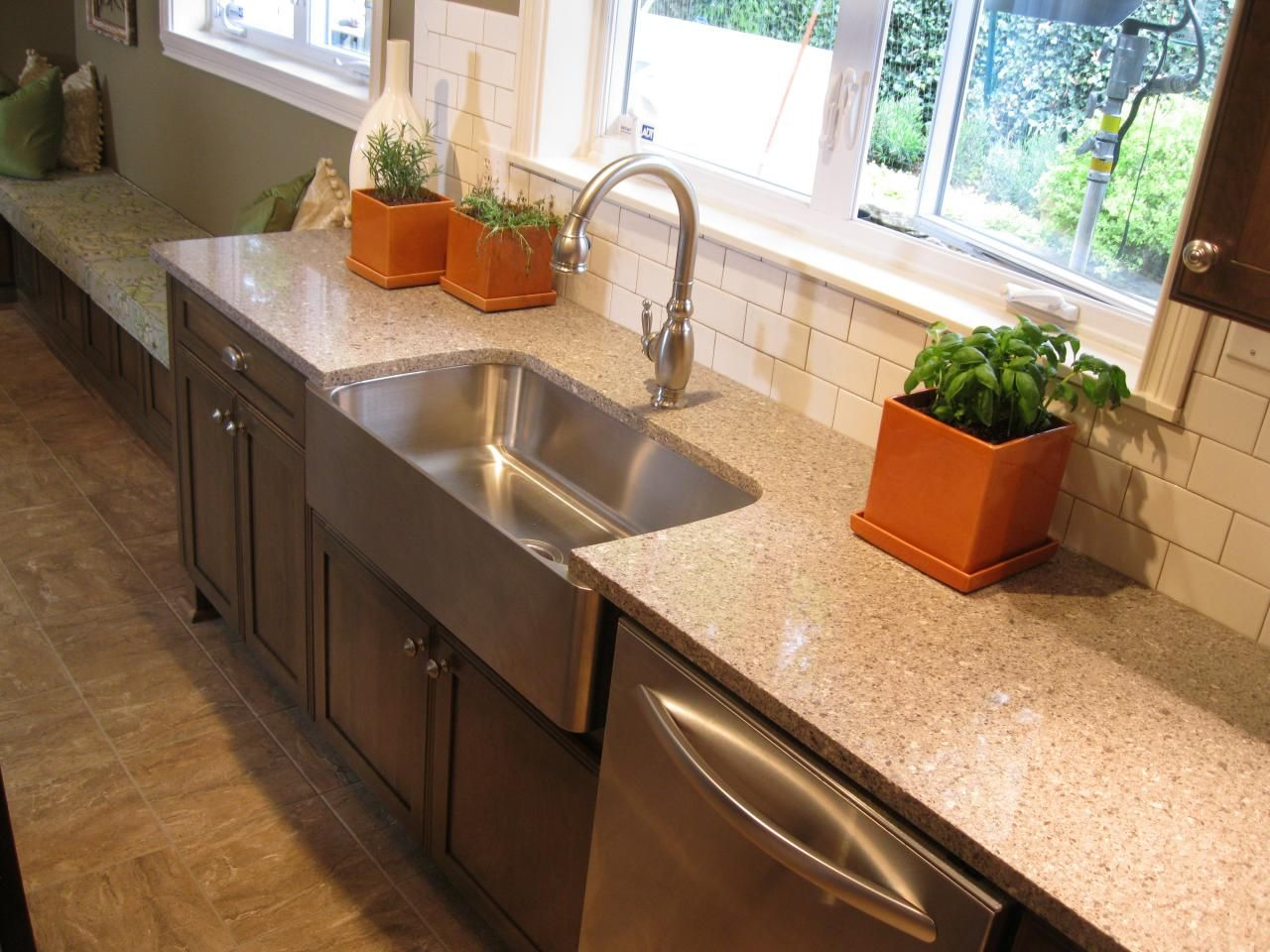 A stainless steel farmhouse sink complements the stainless dishwasher and provides contrast to the dark-stained wood cabinets in this kitchen's sink area. A window above the sink provides lots of natural light for the various potted herbs on the neutral stone countertops.