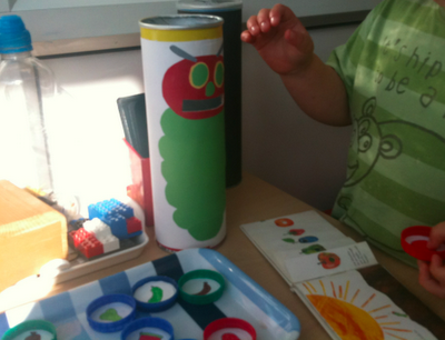 "Very Hungry Caterpillar.  ""Simply cover a Pringles tin with some plain paper, stick and cut out (or print out of the caterpillar on to the tin- and cut out a slot for the mouth big enough to post milk bottle caps in. Stick pictures of each of the food items onto milk caps"""