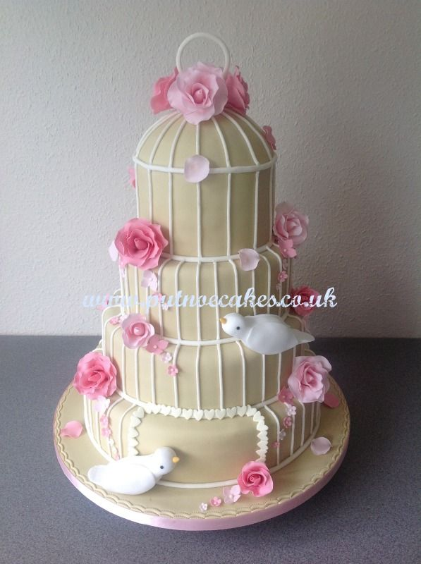 Soft mocha coloured 4 tier birdcage wedding cake decorated with doves, shaded pink roses, hearts, hydrangeas and small shaded pink flowers