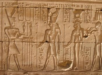 A Ptolemy makes offerings to the Edfu Triad: Horus, Hathor