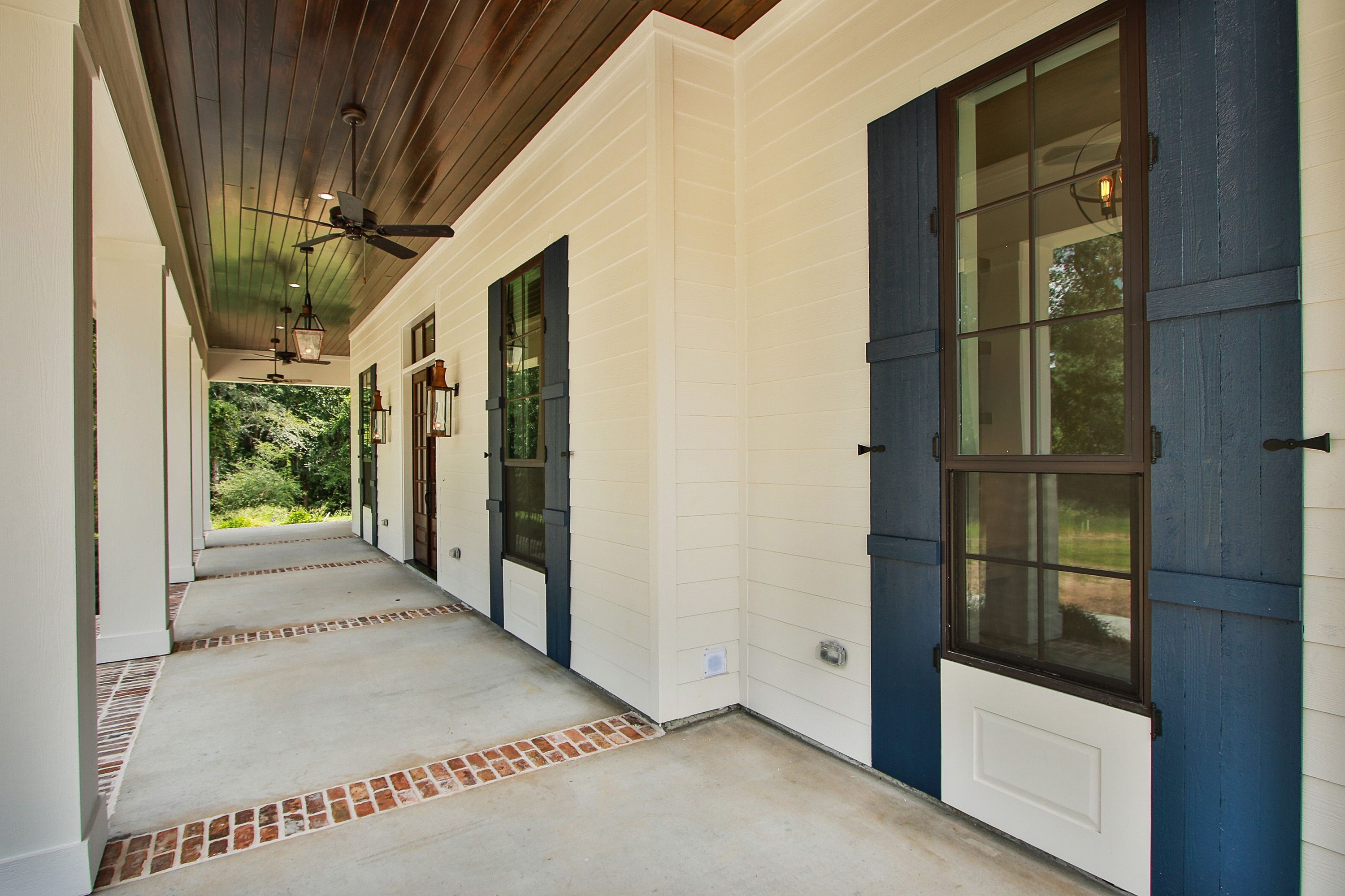 Dark Bronze Aluminum Windows Blue Painted Shutters Bevolo Gas Lighting Stained Tongue And Groove Ceiling An Acadian Style Homes Blue Shutters Patio Flooring