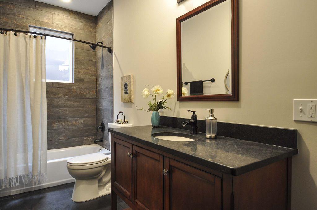 Hall Bathroom Dark Gray Slate Floor Medium Toned Wood Vanity With Honed Black Granite Counters Tub Shower Wood Vanity Wood Tub Granite Bathroom Countertops