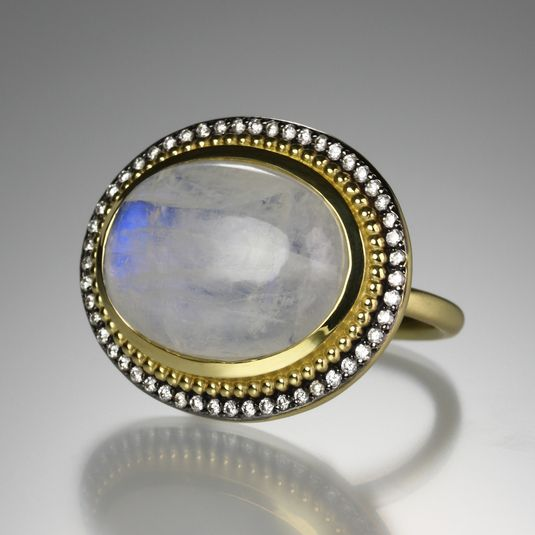 """An 18k yellow gold and black rhodium plated """"Emma"""" ring with an oval cabochon rainbow moonstone and .40cttw diamonds. Size 6.5."""
