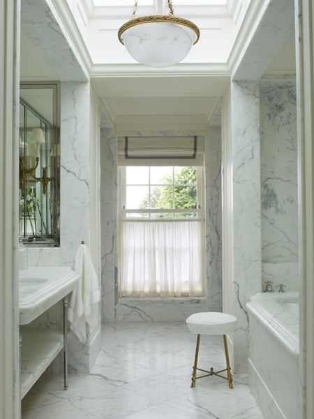 stunning bathroom with skylight in tray ceiling framing a bowl shaped opal glass pendant over gray