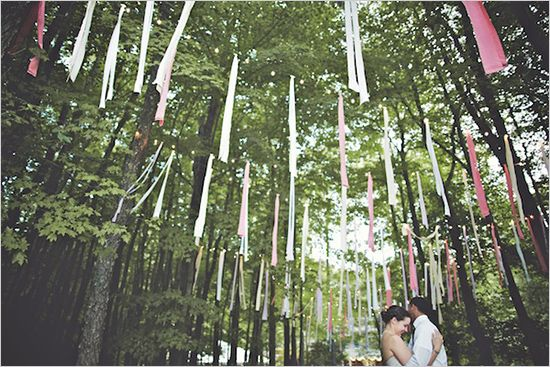 streamers and fabric strips hanging from trees as whimsical wedding reception decor photo hotmetalstudio