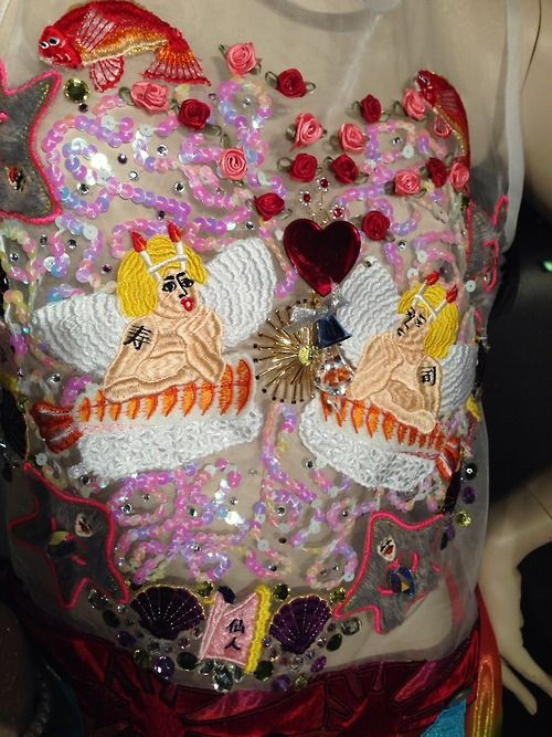 The image used both sequin and stitch work and captures two cupid figures. The designer creates kitsch like play on the themes surrounding love. The idea could be applied to the samples through using oversized sequins and shiny beads.
