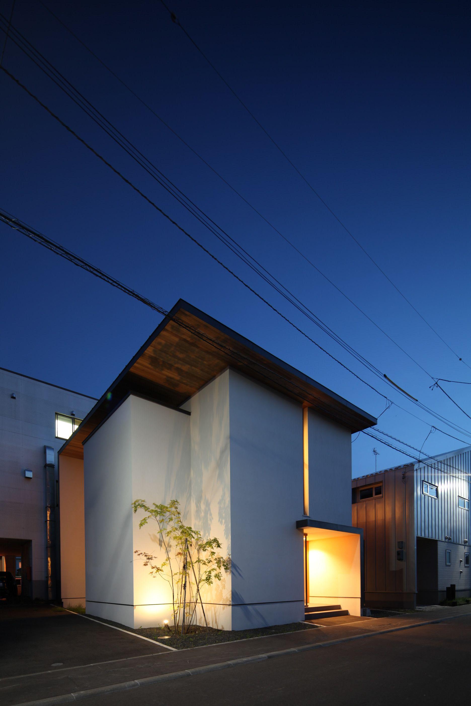 軒天を木にすることでアクセントをつけています 設計事務所 住宅 白壁 北海道 照明 植樹 軒天 スリット 夜景 Architecture Design Architects House Hokkaido Lighting 住宅 外観 モダンハウスの外観 建築デザイン