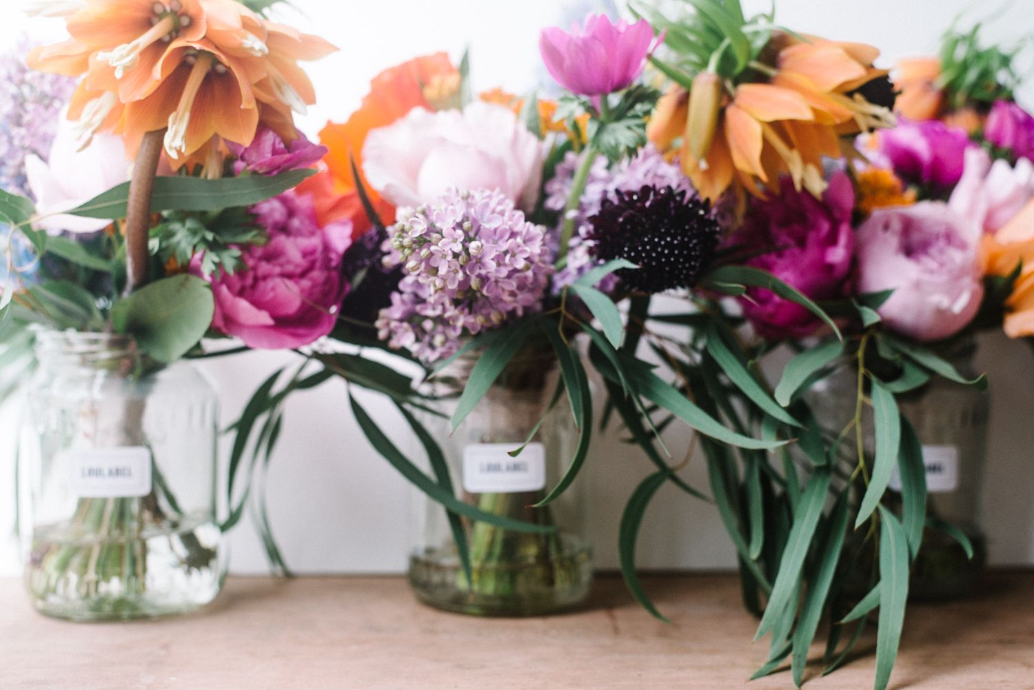 | SPRING TROPICAL WEDDING | Natural, gathered from the garden look bridesmaid's bouquets , made with bright flowers poppies, garden roses, anemones, fritillaria, scabious, delphiniums, lilac & eucalyptus for their beautiful wedding at Polhawn Fort on the coast of Cornwall.
