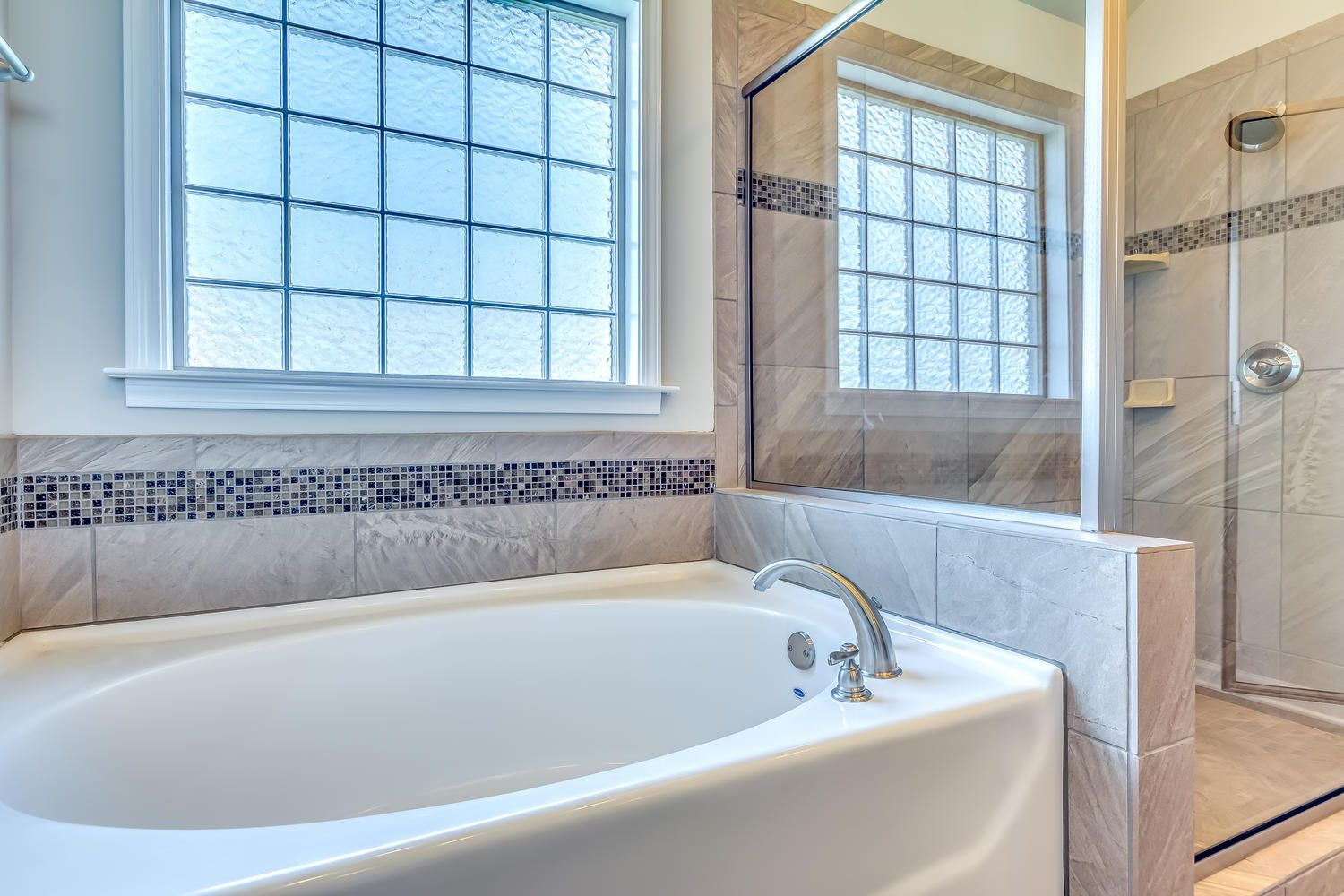 Stunning master bathroom with tan walls along with a large bath tub ...