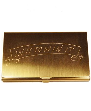 "Brass business card holder. Reads ""IN IT TO WIN IT"""