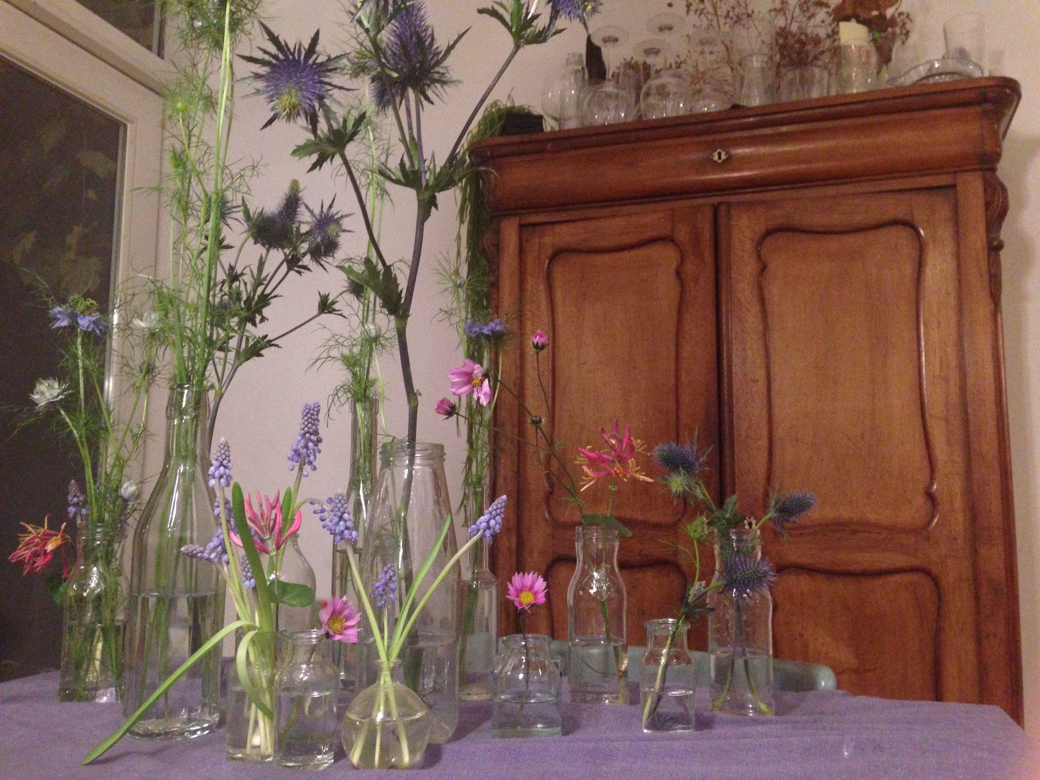Bloemen, oude glazen flesjes, vaasjes.