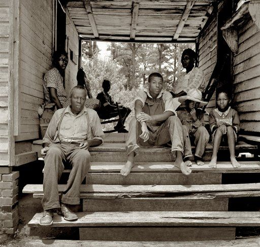 "July 1939. ""Zollie Lyons, Sharecropper, home from the field for dinner at noontime, with his wife and part of his family. Wake County, North Carolina."" by Dorothea Lange"