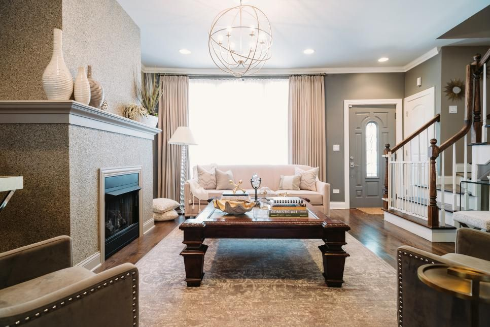 To add energy and visual interest to its neutral palette this living room makes compelling use of different shapes a orb like chandelier hovers above the