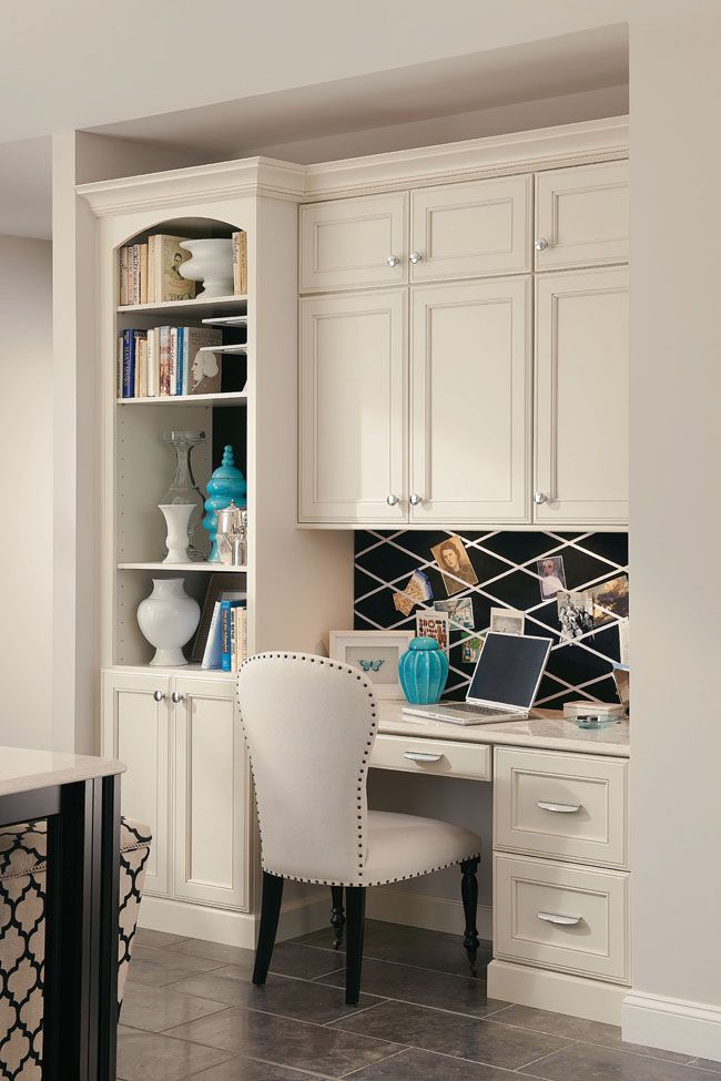 A built in desk with bookcase and cabinets creates a