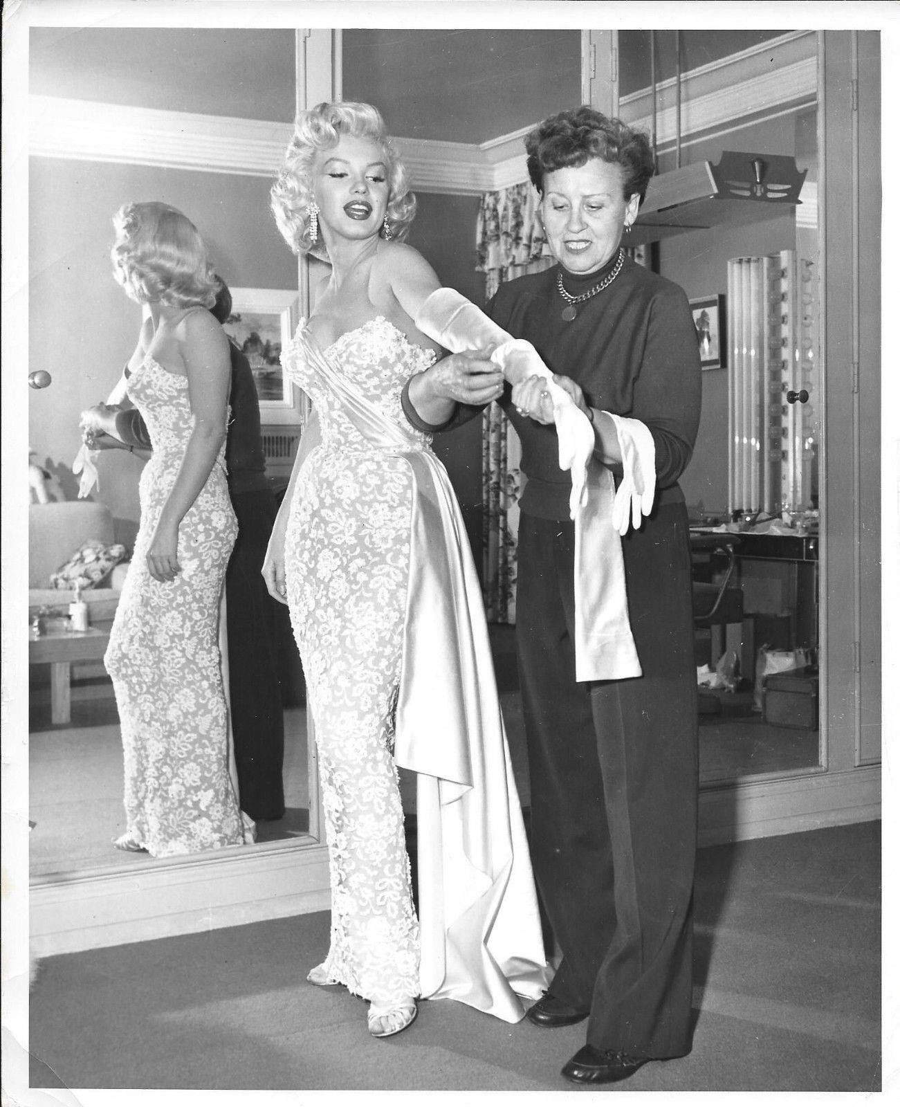 Marilyn Monroe getting a little help with her ensemble for the premiere of How to Marry a Millionaire, 1953.
