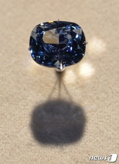 """The priceless 12 carat """"Blue Moon Diamond"""" is displayed at the Natural History Museum in Los Angeles on September 12, 2014. The extremely rare 'Fancy Vivid Blue Diamond' was discovered in South Africa. AFP PHOTO/Mark RALSTON."""