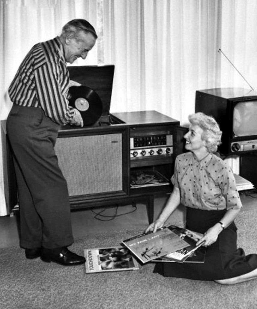 Senior couple listening to music from vinyl records, 1960s.
