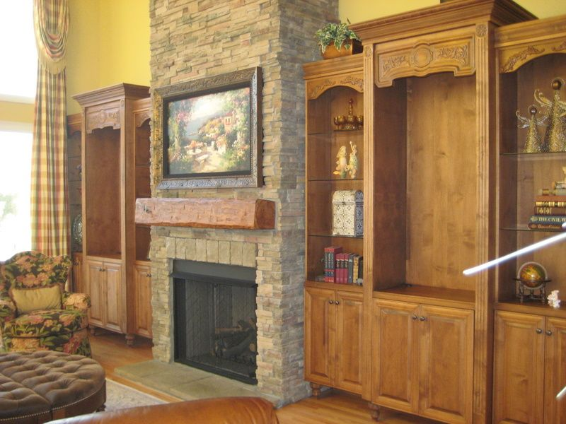 Stone Fireplace with TV above and beautiful cabinetry along wall.  Note TV is framed and showing art as screensaver. See how drapes go all the way up the wall?  All around very nice