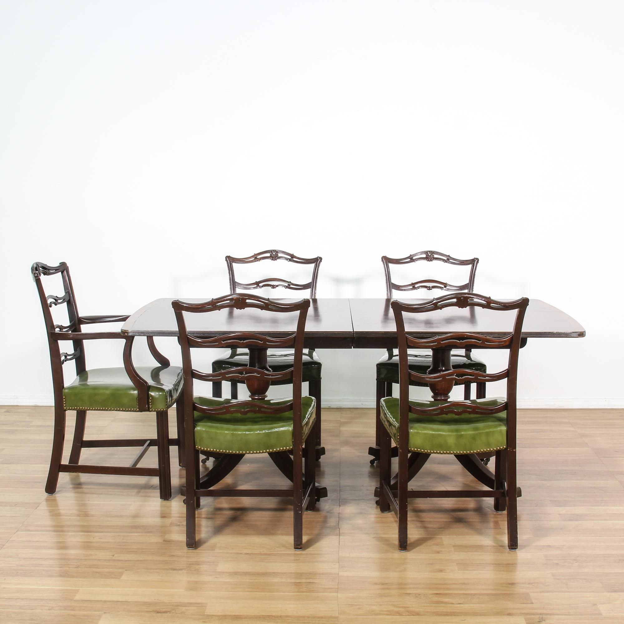 This Duncan Phyfe dining set is featured in a solid wood with a glossy mahogany finish. This traditional style table and set of chairs have green vinyl upholstery, studded nailhead trim, and box stretchers. Gorgeous set that's perfect for casual or formal dining! #americantraditional #tables #diningset #sandiegovintage #vintagefurniture