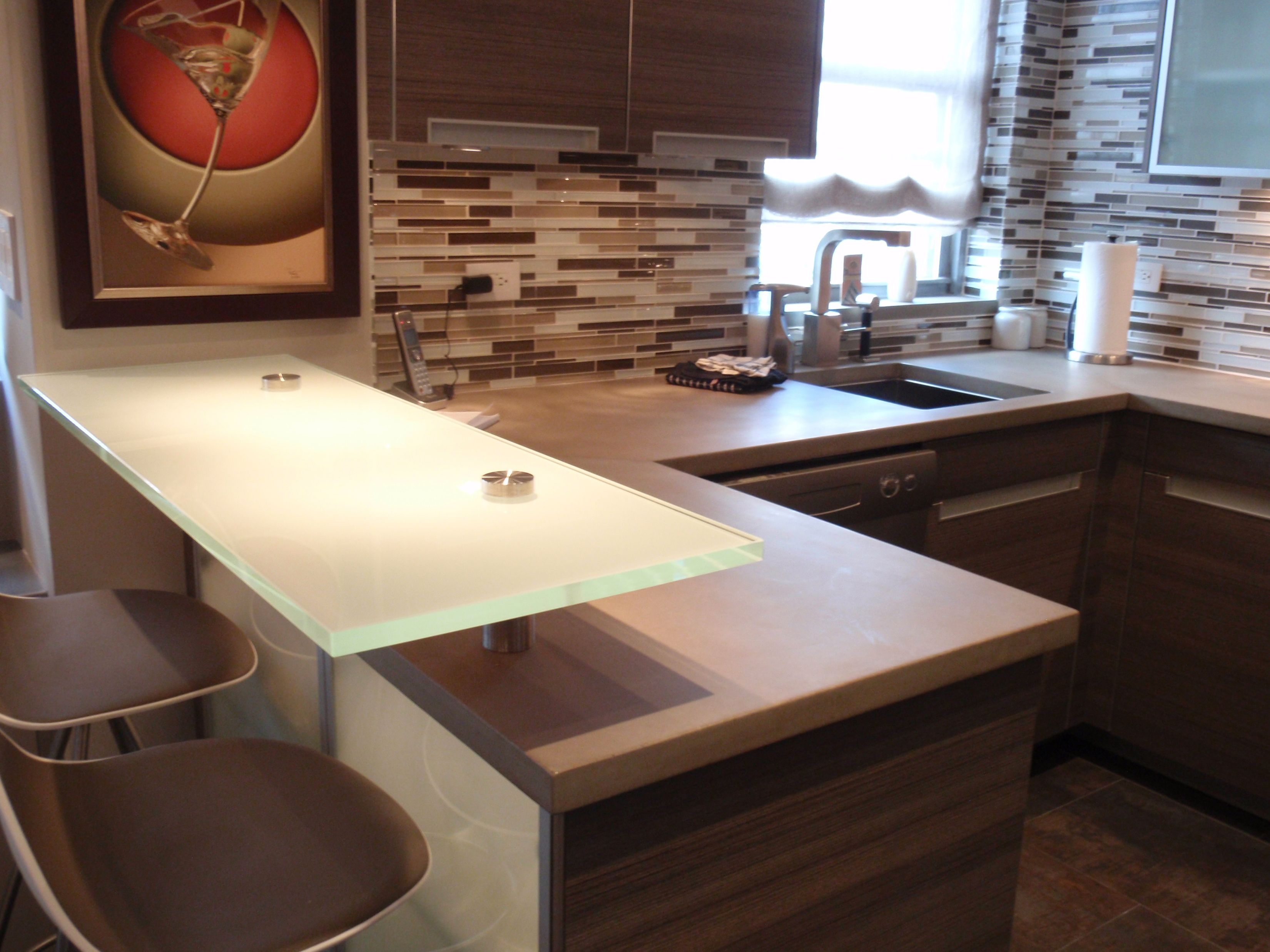 Sandblasted glass raised bar top with concrete countertops in a ...