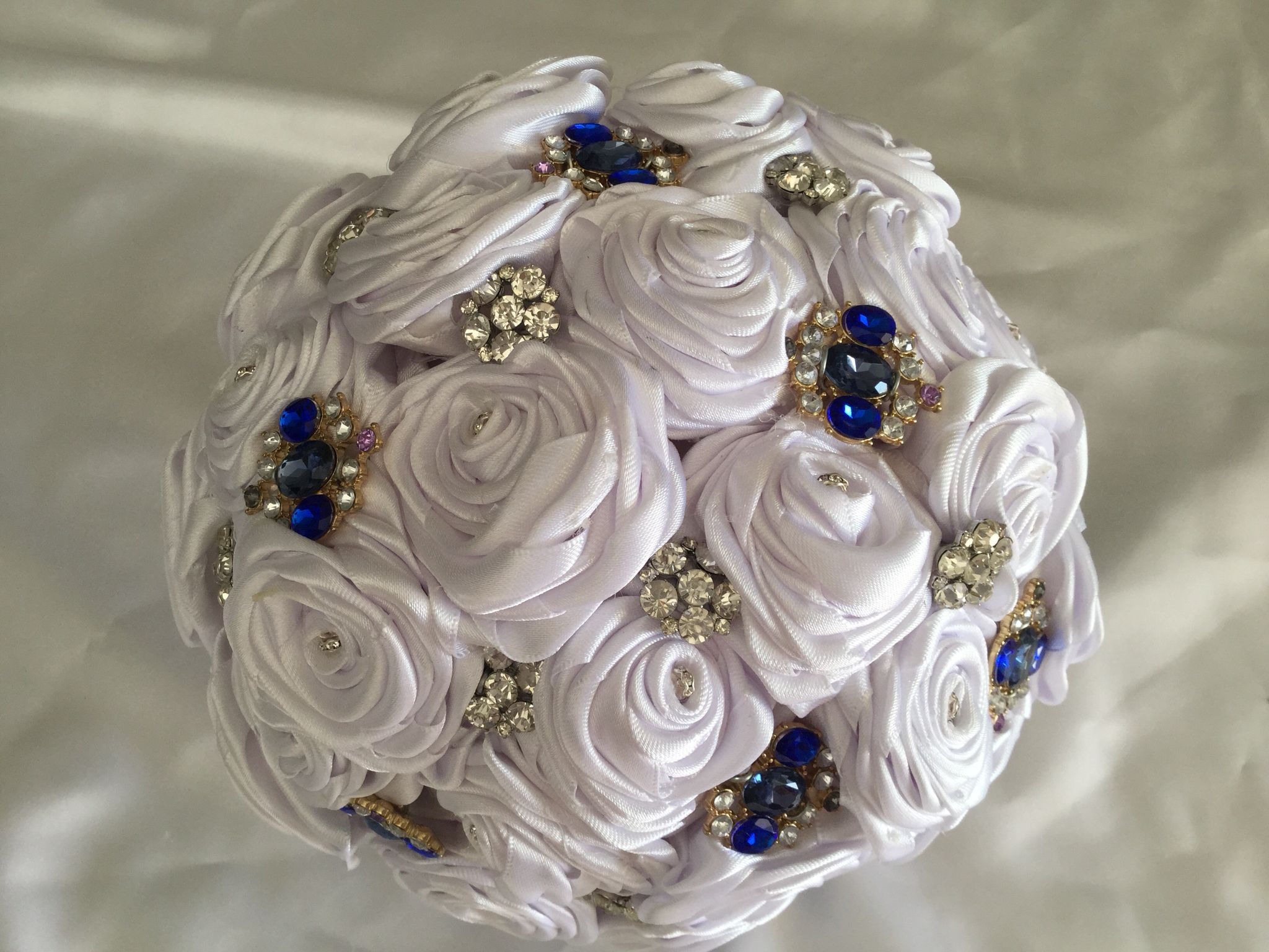 A stunningly elegant half sphere bouquet of white closed roses with a bling centre, covered with a scattering of clear and blue small brooches.  All bouquets can be reproduced in the size and colour of your choice. Feel free to mix and match ideas to make your bouquet more individual. Corsage, MOB and Lapel pins are also available to match your colours. Contact leeann@bejewelledbridal.com.au for more information.