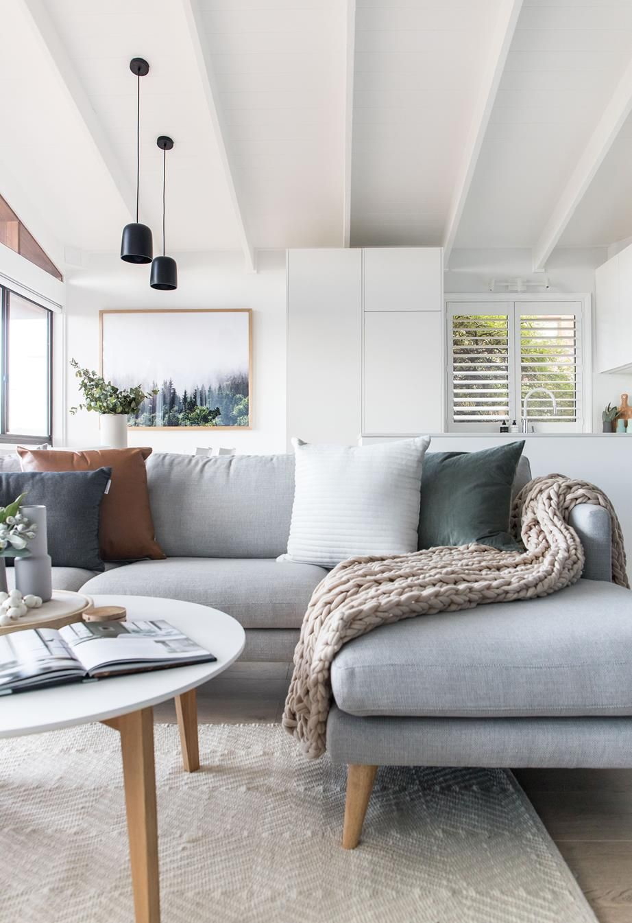 Living room with neutral rug, pale blue L-shaped lounge with knitted throw and colourful cushions. | Explore Eliza Lee One, an elegant renovated ski retreat in Jindabyne | Inside Out | Photography: The Palm Co