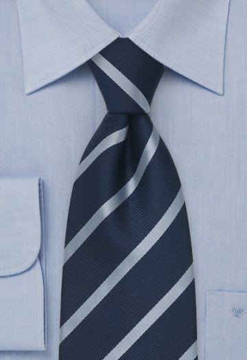 Zijden stropdas met fijne strepen in koel blauw-grijs op een marine- blauwe achtergrond.