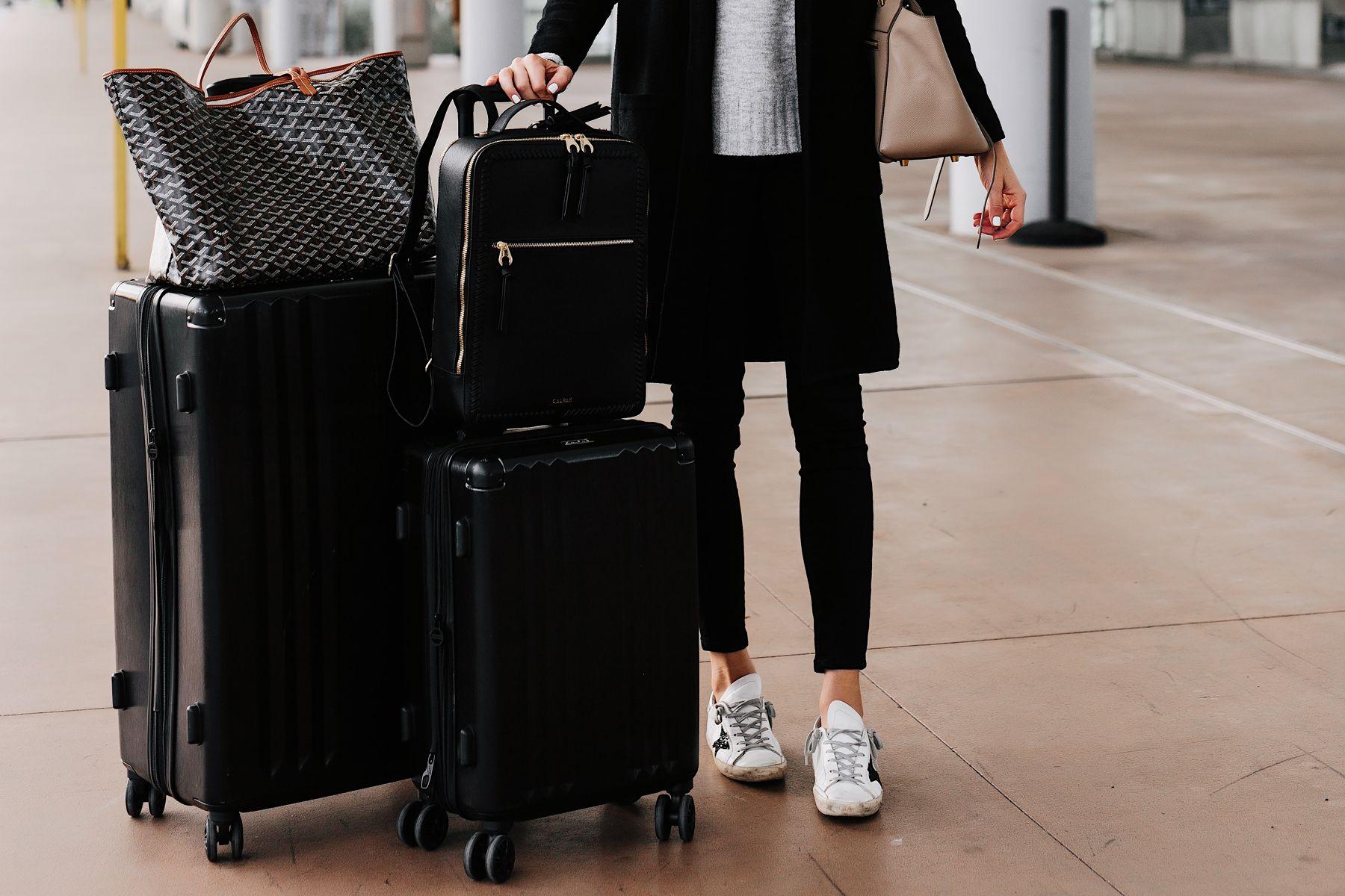 4353c935b Woman at Airport with Calpak Kaya Black Backpack Calpak Black Luggage  Goyard Tote Airport Style