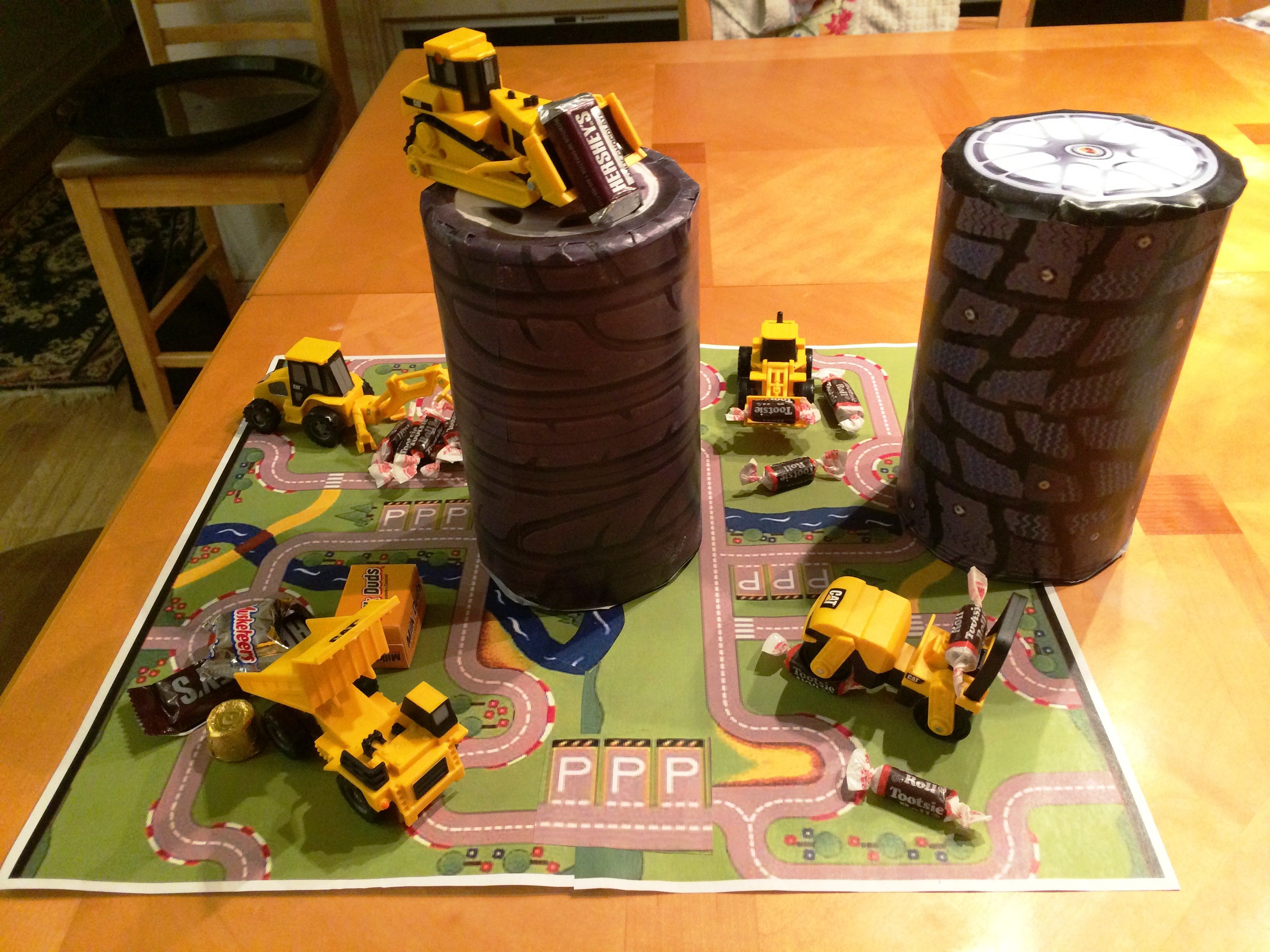 Diaper wipe canisters made into tires with construction vehicle theme for table decorations for Baby Monroe's shower.