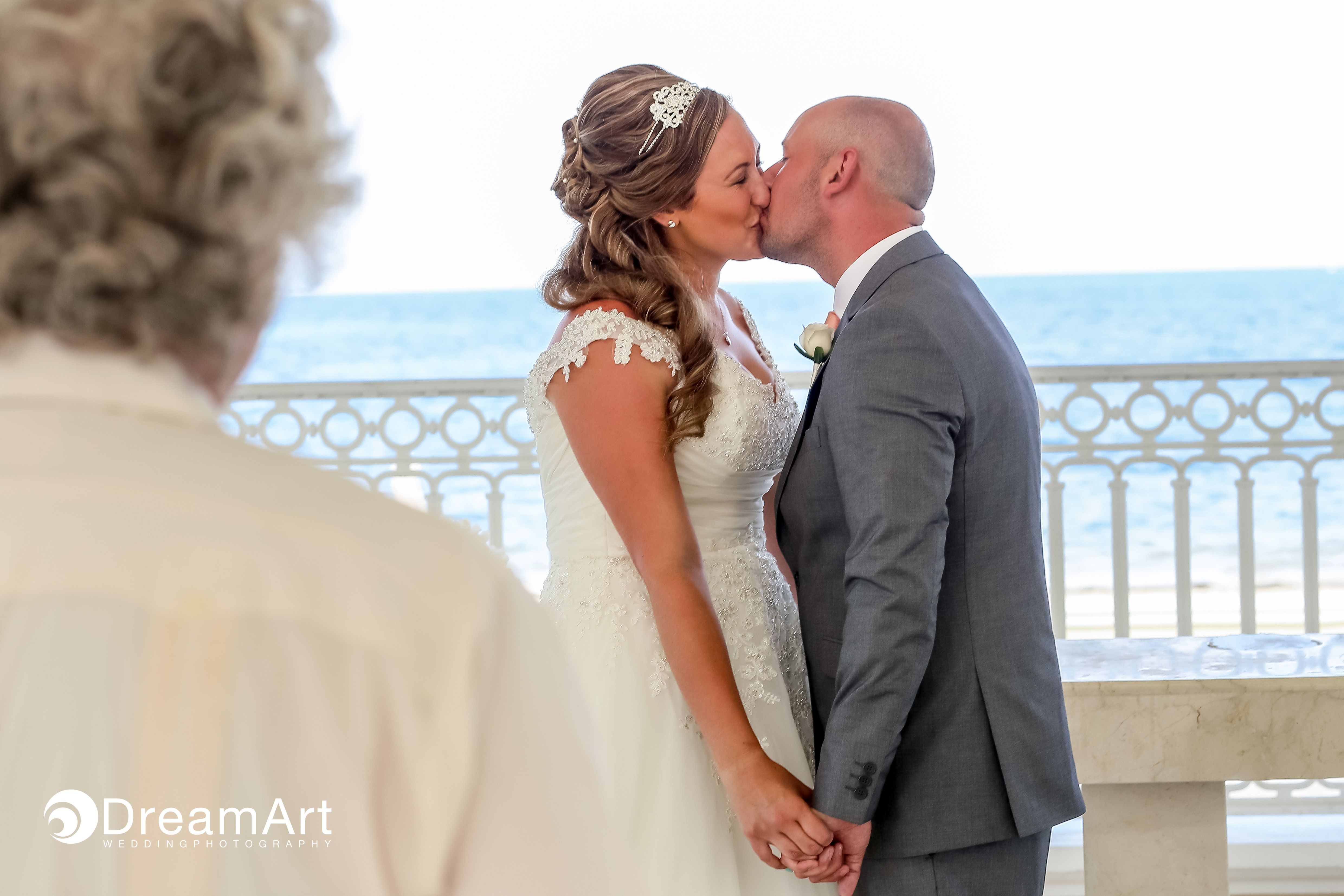 A Bride And Groom Share Their First Kiss During A Wedding Ceremony