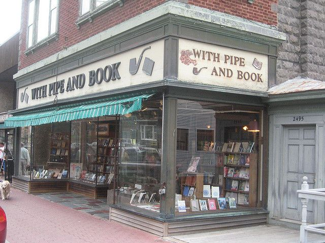 """With Pipe and Book -- """"Nigel Beale's Bookstore Photographs,"""" by Nigel Beale, via Flickr -- This second hand bookstore / tobacco shop in Lake Placid, NY, has closed, to the great regret of a lot of regulars and tourists. Evidently had a really good selection; certainly had a cool sign!"""