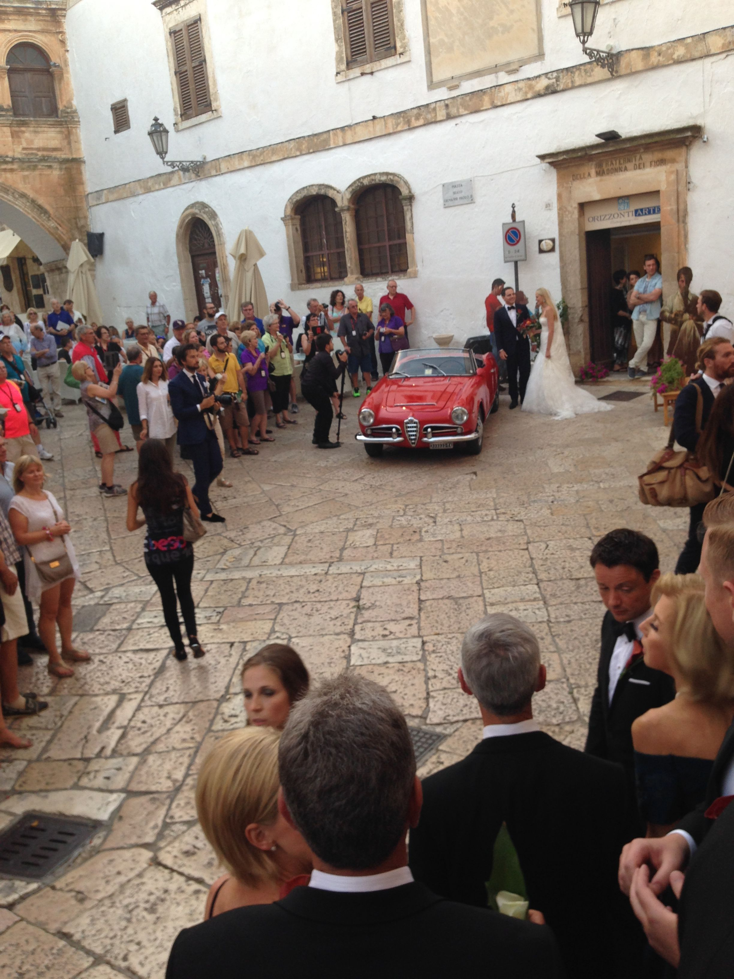 The beautiful couple in the town square before they jetted off in this antique Alfo Romeo on their way to the reception