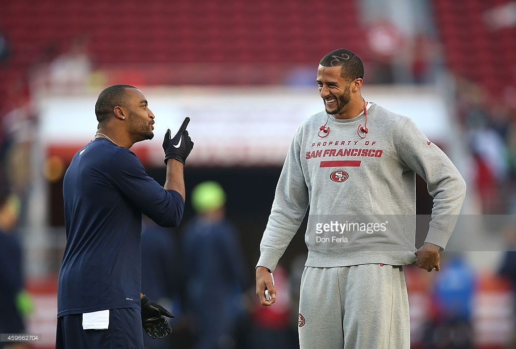 Colin Kaepernick of the San Francisco 49ers has a laugh with Doug Baldwin of the Seattle Seahawks during warm ups at Levi's Stadium on November 27, 2014 in Santa Clara, California.