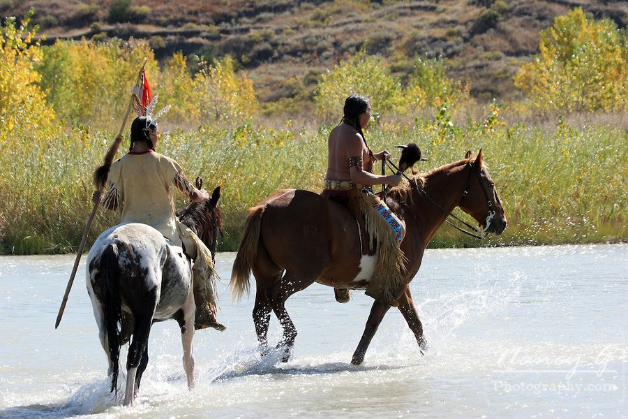 Two Native American Indian men on horseback walking