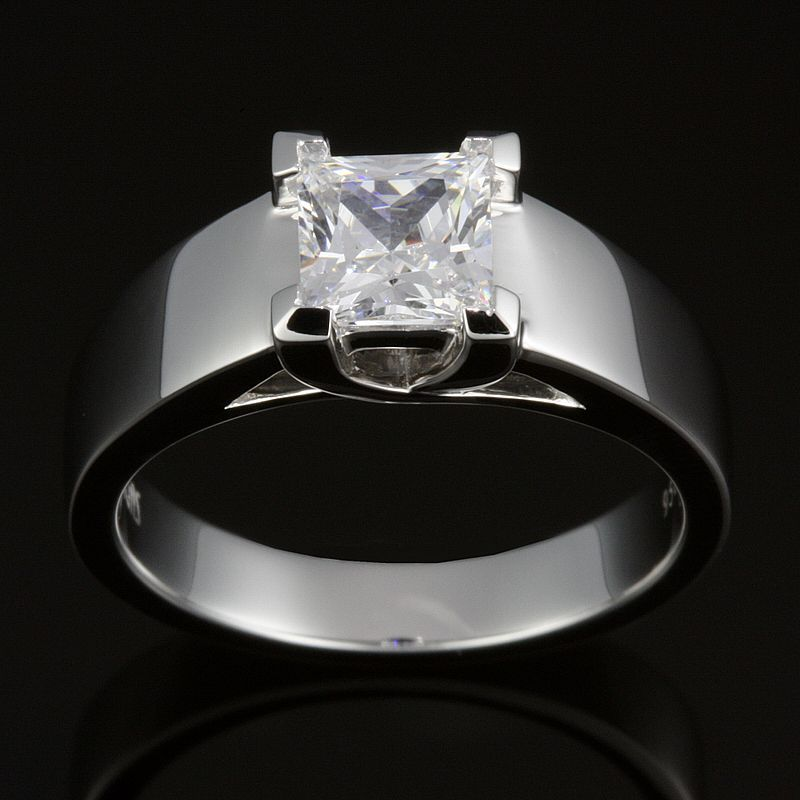 Princess cut diamond with cross over prongs and tapered flat band shoulders. An edgier take on a classic diamond solitaire.  Try on this design in our showroom.