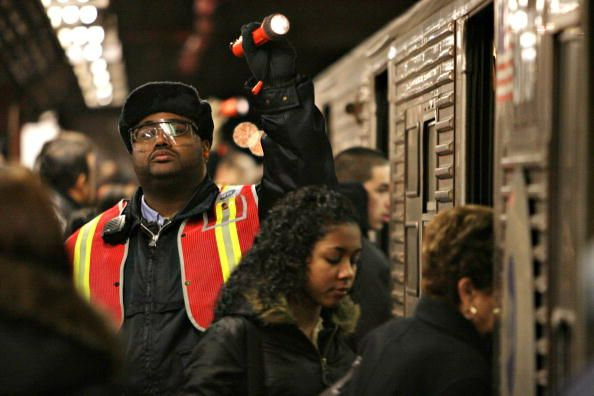 A Subway Worker Uses A Flashlight To Signal The Trains Conductor As Train Conductor Subway Worker