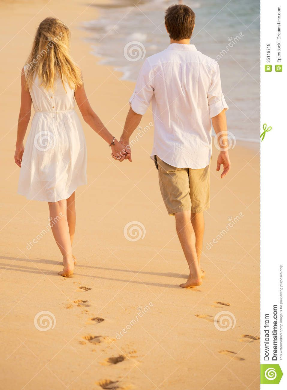 Romantic Couple Holding Hands Walking On Beach At Sunset Royalty
