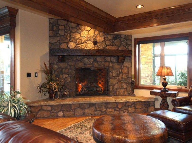 grey stone fireplace with shabby brown wooden mantel shelf and grey stone hearth connected by glass window