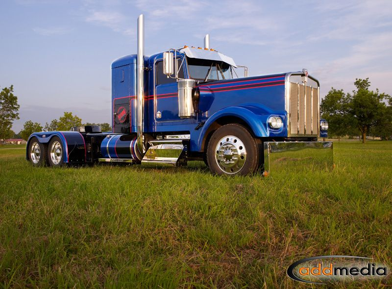 A Fully Restored Kenworth W900b Decorating A Meadow Outside Of
