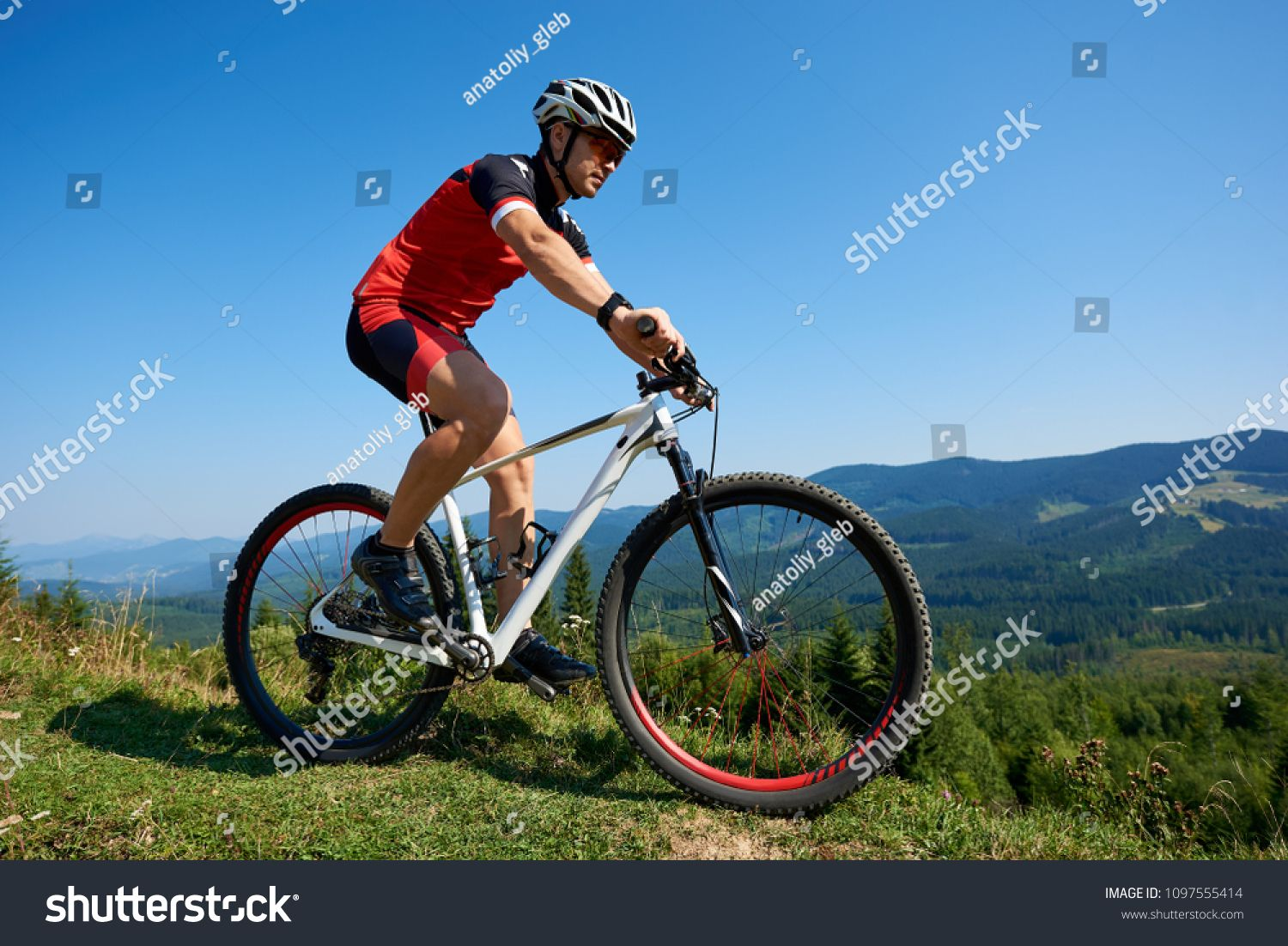 Muscular tourist cyclist in helmet, sunglasses and full