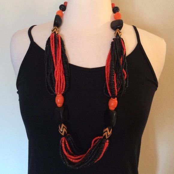 "Tribal Design Beaded Necklace Black and orange wooden beaded necklace is a statement piece. Designed in sections of wooden beads and twisted braided beads. Measures 17"" inches long. Jewelry Necklaces"