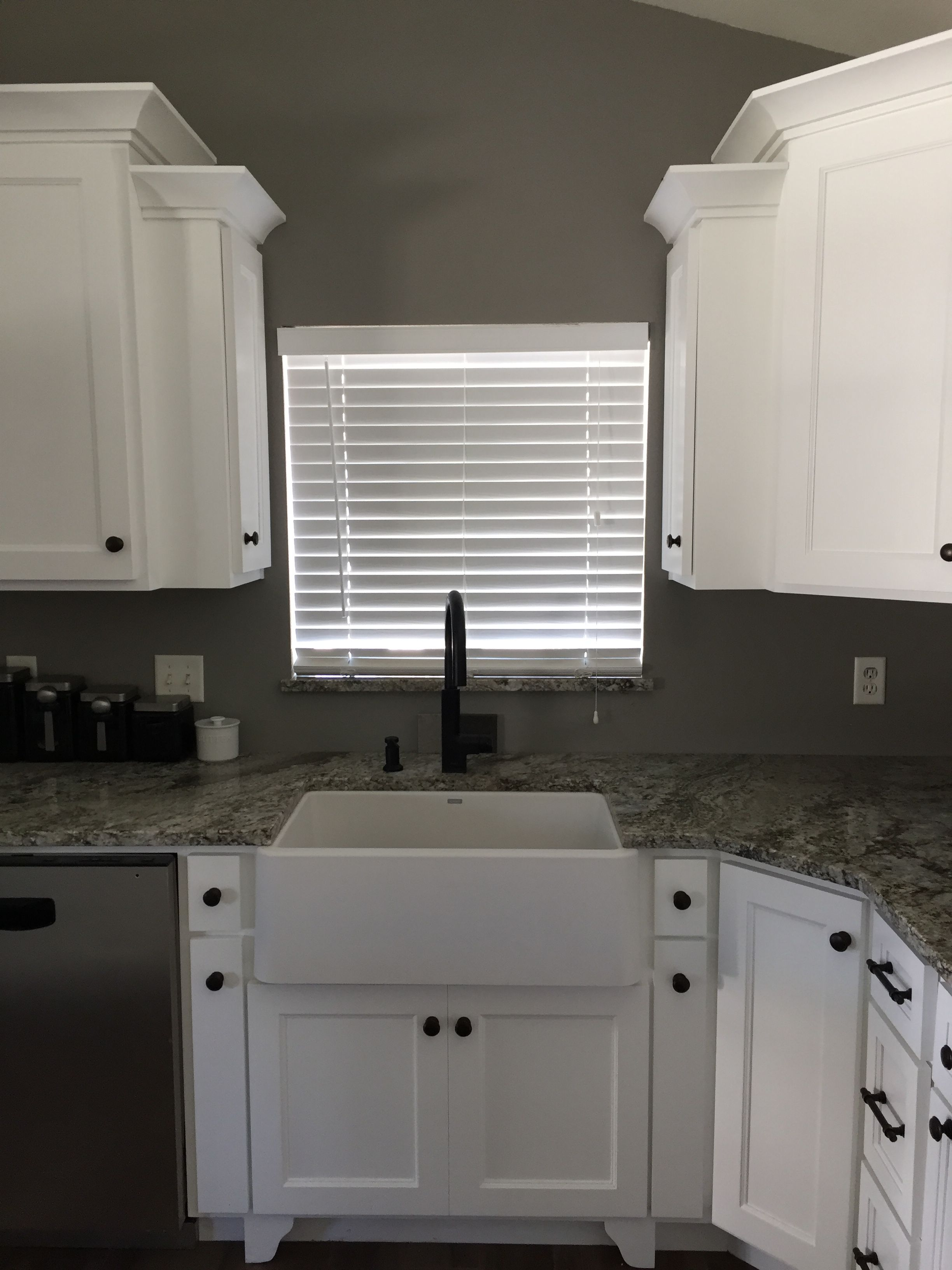 White kitchen cabinets with white blanco ikon sink and black moen