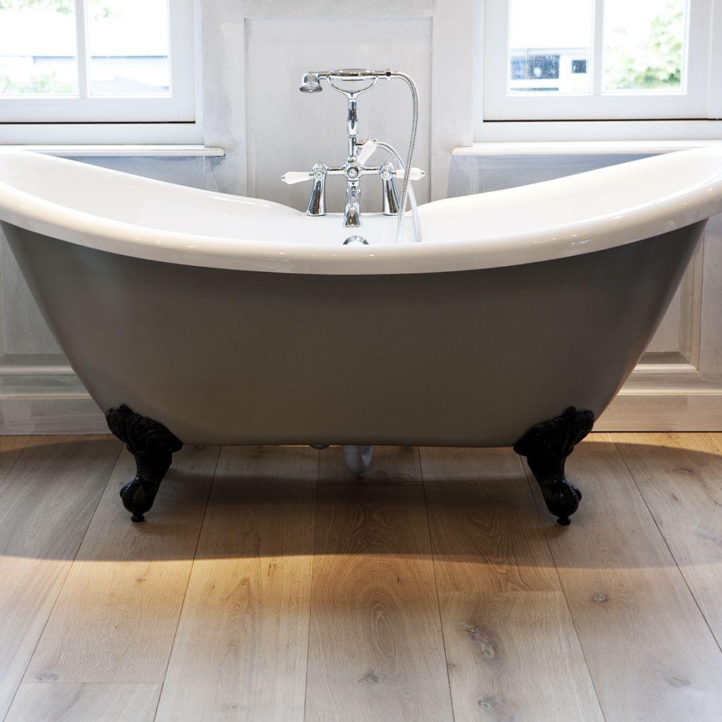 een echt houten vloer in de badkamer en een klassiek bad op