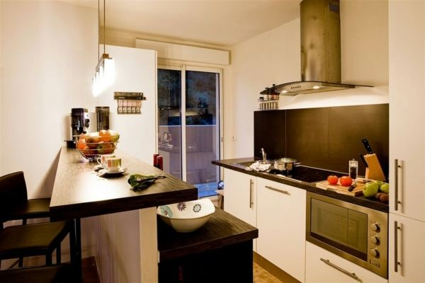 petite cuisine avec bar et plan de travail en bois, appareils en