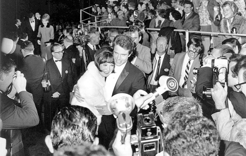 April 18, 1966: Actor Warren Beatty embraces his sister actress Shirley MacLaine as they face the media and crowd outside the 1966 Academy Awards ceremony, where they were presenters.