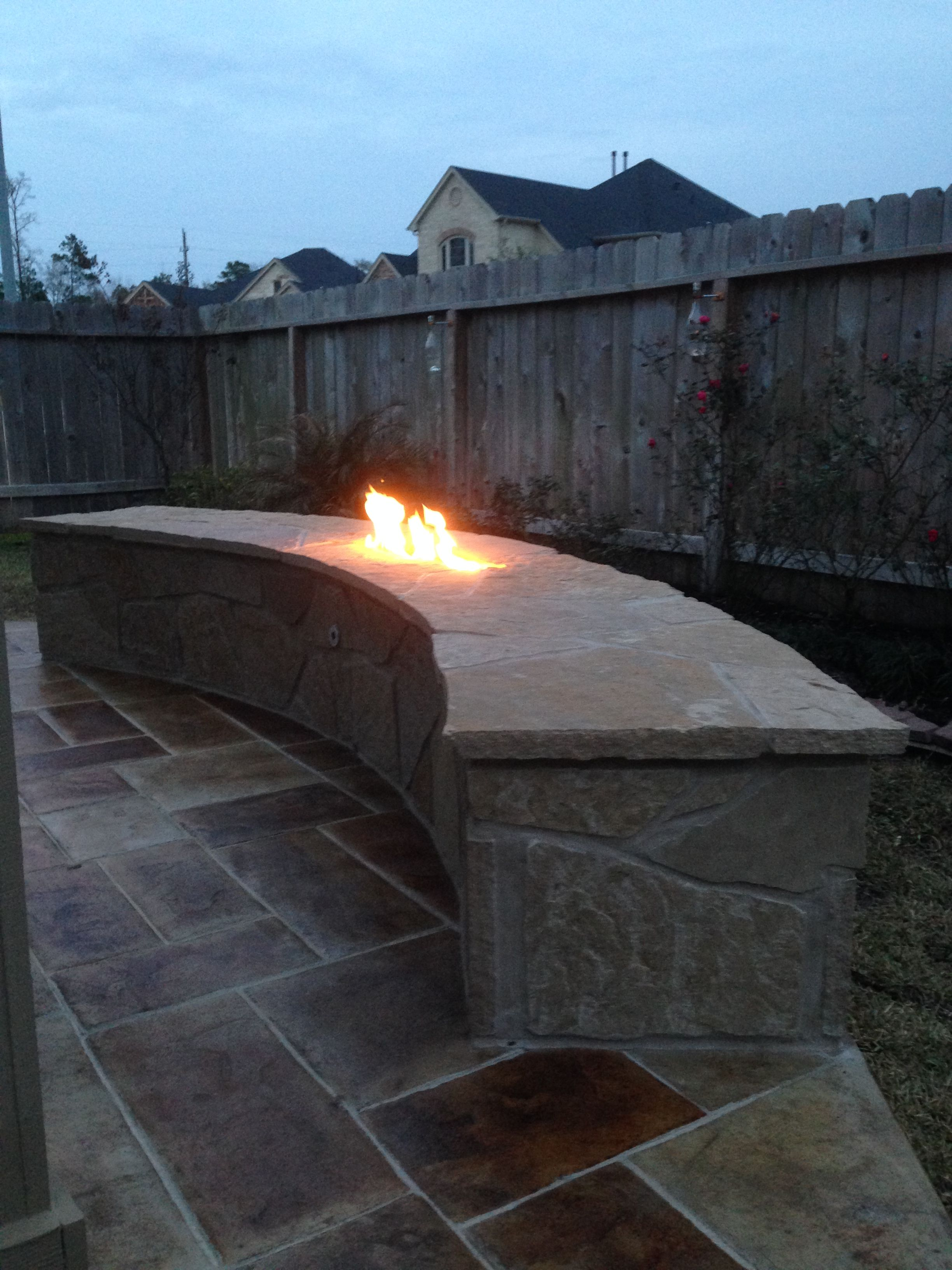 stone fire pit in bench with stamped concrete western patio