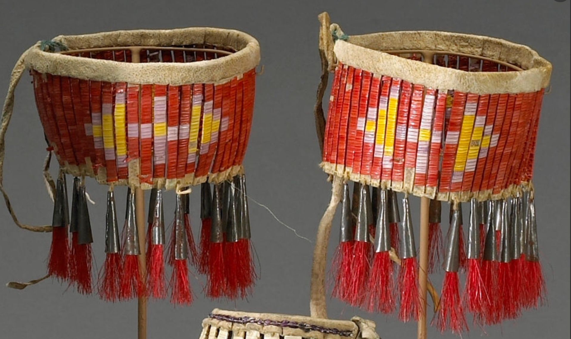 A PAIR OF SIOUX QUILLED ARMBANDS.  Property from a Southwest collector.  Consisting of quill-wrapped rawhide slats fastened at top with a leather sleeve, worked in cross and tipi motifs, trailing tin cones and dyed horsehair suspensions. length 5in. Bonham's NATIVE AMERICAN ART. 1 июня 2009 года. Сан Франциско.