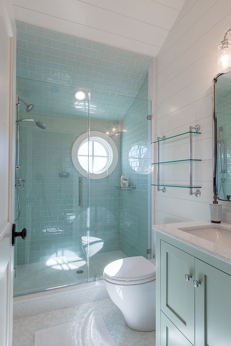 A green tiled bath, round shower window, white wooden ceiling and ...
